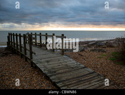 A wooden bridge on Worthing beach in December as sun is setting - Stock Photo