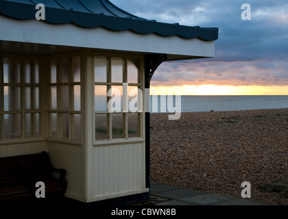 A shelter on Worthing seafront in December as sun is setting - Stock Photo