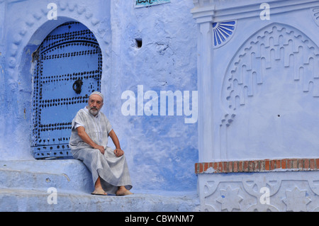 Traditionally clothed man resting near blue washed houses in the streets of Chefchaouen Morocco North Africa