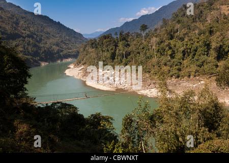 India, Arunachal Pradesh, Panging village, woman walking over suspension bridge across Digang River in Himalayan - Stock Photo