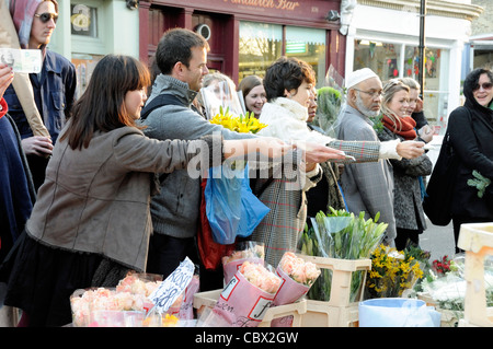 People offer money to the stallholder for cheap bunches of flowers, Columbia Road Flower Market, Tower Hamlets London - Stock Photo