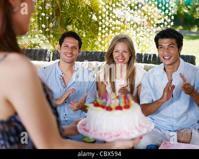 Birthday party with cake, drinks and happy caucasian and asian friends clapping hands. Front view - Stock Photo