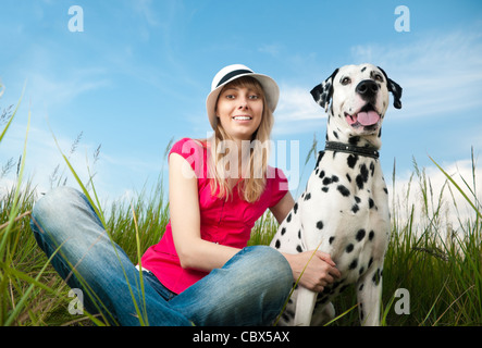 beautiful young woman in hat sitting in grass with her dalmatian dog pet and smiling. Both looking into the camera. - Stock Photo