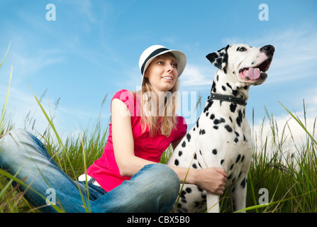 beautiful young woman in hat sitting in grass with her dalmatian dog pet and smiling. Blue sky in background and - Stock Photo