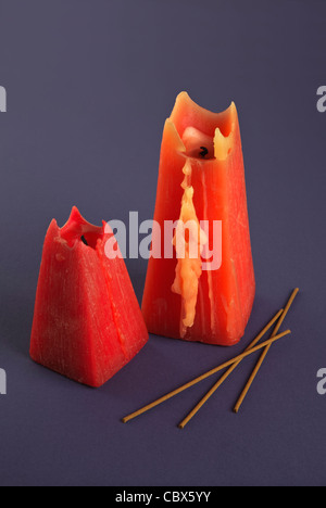 Two red Candles and incense sticks on blue background