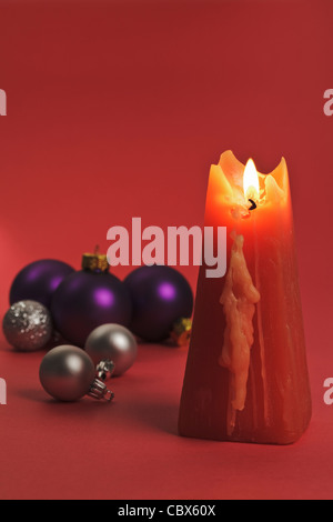 One burning red Candle with Christmas Bubbles - Stock Photo