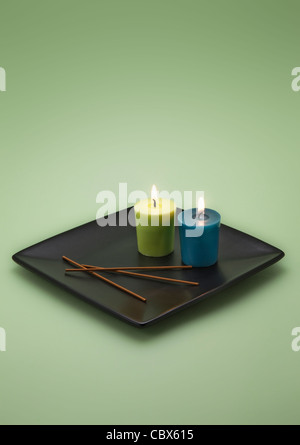 Two burning Candles on black Plate - Stock Photo