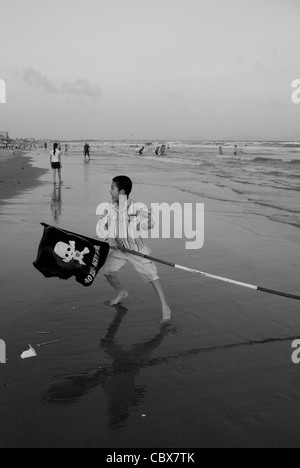Vungtau, Vietnam. Boy playing on the beach with a flag used for warnings like the presence of sharks or dangerous - Stock Photo