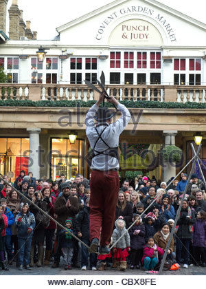 A tightrope walker entertaining a crowd of tourists in Covent Garden London UK - Stock Photo