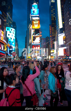Tourists from Asia taking pictures on Times Square in New York City, USA - Stock Photo