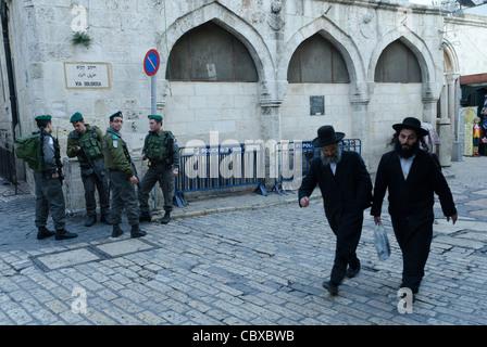 two orthodox jews walking passed Station III of Via Dolorosa with border patrols in backg. Jerusalem Old City. Israel - Stock Photo