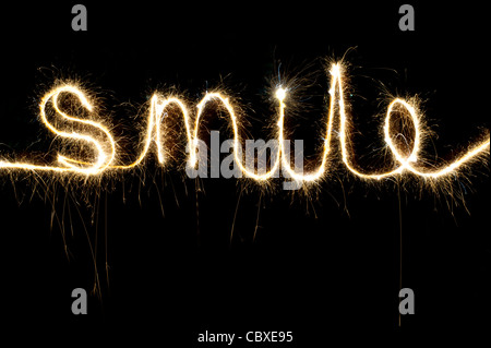 SMILE  written with a sparkler at night - Stock Photo