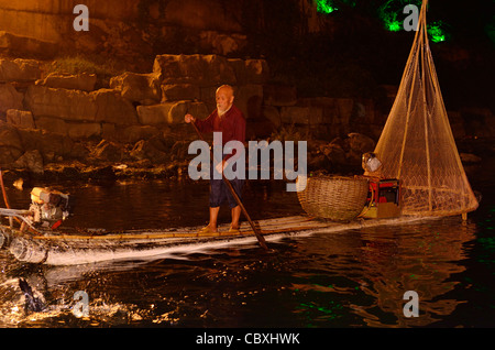 Chinese fisherman watching cormorant catch fish at night on the Li river in Yangshuo Peoples Republic of China - Stock Photo