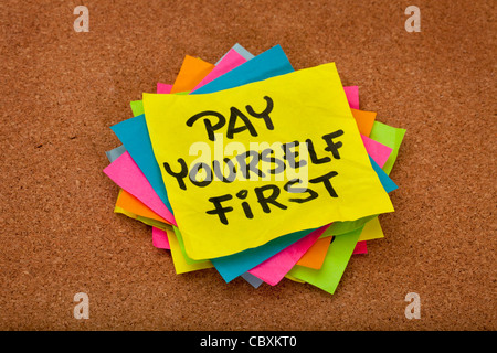 pay yourself first, a reminder of personal finance strategy - stack of colorful sticky notes on a cork bulletin - Stock Photo