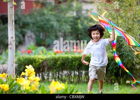 Little boy flying kite in garden - Stock Photo