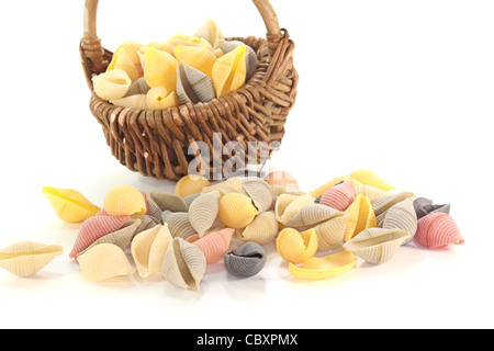 handful of colorful noodles in basket on white background - Stock Photo