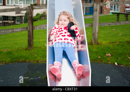 3 Year Old Child Girl Infant Toddler playing Sliding Down A Slide In A Childrens Playground - Stock Photo