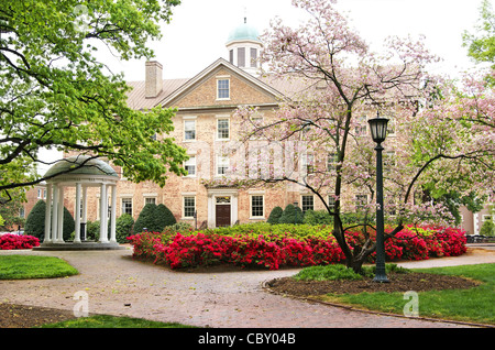 The old well at UNC, University of North Carolina at Chapel Hill, in the spring with flowering pink Dogwood trees - Stock Photo
