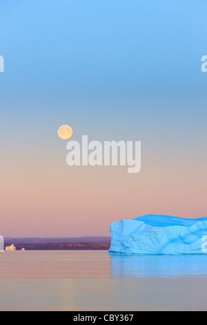 Iceberg at Sunset and Moonrise at Hall Bredning, Scoresbysund, Greenland - Stock Photo