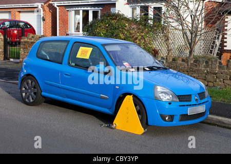 Untaxed vehicle with DVLA wheel clamp on a UK street - Stock Photo