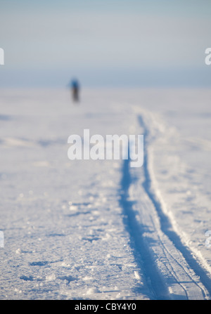 Blurry human figure of a cross-country skier and his ski track on Baltic Sea ice , Finland - Stock Photo