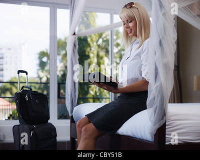 Mid adult caucasian businesswoman typing on tablet pc in hotel room during business travel. Side view, three quarter - Stock Photo