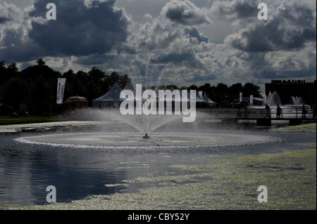 Ornamental Fountain and Lakes at Hampton Court during the Royal Hampton Court Flower Show with marquees and clouds - Stock Photo