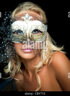 Young blond woman wearing a white mask - Stock Photo