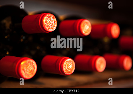 Abstract of red wine bottle tops on a wine rack - Stock Photo