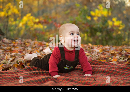 SIx Month Old Baby Boy Laying on Blanket Outside amid Autumn Color - Stock Photo