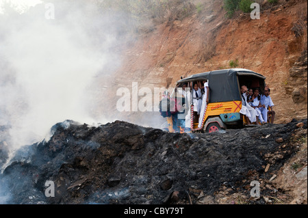 Indian children in rickshaw passing household waste being burnt on the roadside. Andhra Pradesh, India - Stock Photo