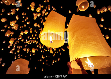 Traditional fire lanterns being released into the night sky during the Loi Krathongfestival in Chiang Mai, Thailand, - Stock Photo