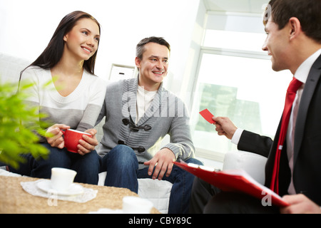 Portrait of modern couple looking at real estate agent giving his visiting card - Stock Photo