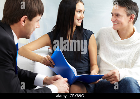 Portrait of modern couple discussing mortgage conditions with real estate agent near by - Stock Photo