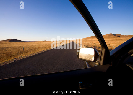 Car sideview mirror with road going through field in the background - Stock Photo