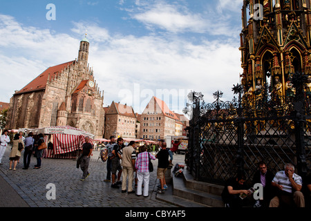 Hauptmarkt and  Frauenkirche - Church of our lady (catholic) with Schoener Brunner Beautiful Fountain in the forefront, - Stock Photo