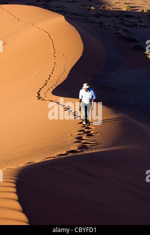 Person Climbing Dunes - Sossusvlei National Park - Namib-Naukluft National Park, Namibia, Africa - Stock Photo