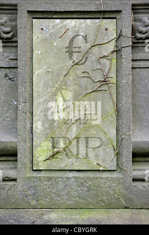 Conceptual grave with € and RIP engraved for symbolic death of European euro due to financial crisis and bank debt - Stock Photo