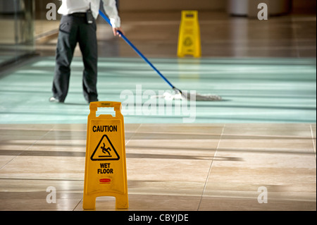 Office cleaner using mop - Stock Photo