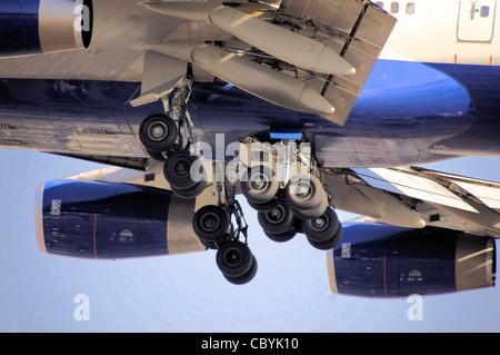 British Airways Boeing 747-400 (G-CIVX) main undercarriages during landing at London Heathrow Airport, England - Stock Photo