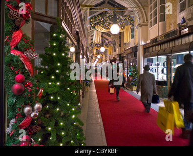 LONDON CHRISTMAS SHOPPING Burlington Arcade in Piccadilly with traditional Christmas decorations and shoppers carrying - Stock Photo