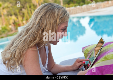 Young teenage girl using tablet computer iPad in holiday vacation setting by swimming pool - Stock Photo