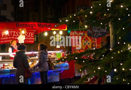 Borough Market patisserie stall viewed through Christmas tree lights at dusk Southwark London - Stock Photo