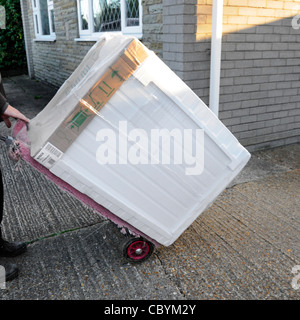 Delivery man using trolley deliver new Bosch tumble dryer from electrical appliance white goods retail supply business - Stock Photo