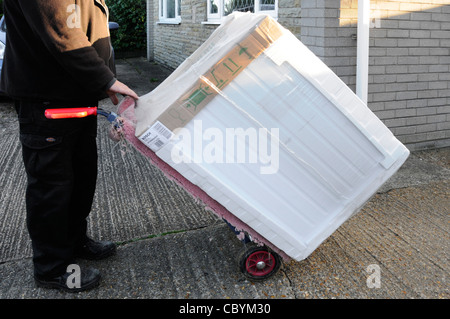 New tumble dryer being delivered by white electrical goods supplier to domestic household Essex England UK - Stock Photo