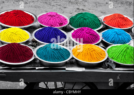 Coloured Indian powder in metal bowls used for making rangoli designs at festivals. Spot coloured onto black and - Stock Photo