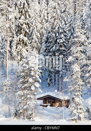Small wooden sauna cottage in the forest at Winter , Finland - Stock Photo