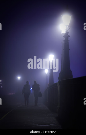 Two women,  walk across Kingston Bridge from Hampton Wick on a foggy evening, deep in conversation. - Stock Photo