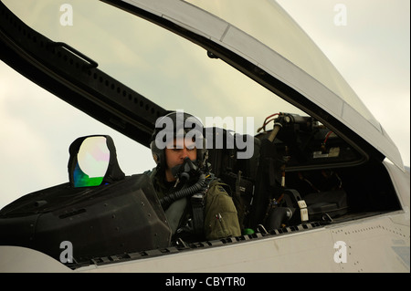 Capt. Jonathan Airhart prepares to start the engine while strapped in an F-22 Raptor prior to a mission Jan. 14 - Stock Photo