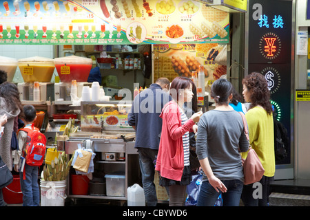 group of chinese women eating street food and drink from a street shop in causeway bay hong kong hksar china asia - Stock Photo
